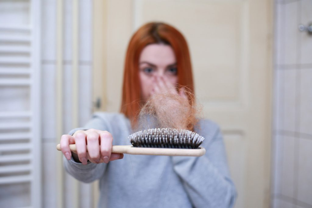 a girl with hair loss, strands of hair stuck in her comb